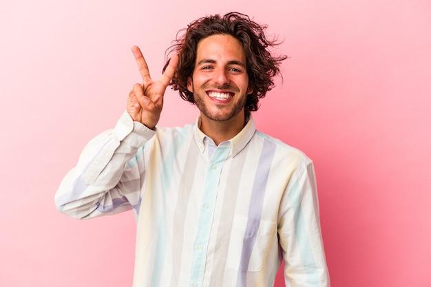 Młody człowiek kaukaski na białym tle na różowym bakcground wyświetlono numer dwa palcami.