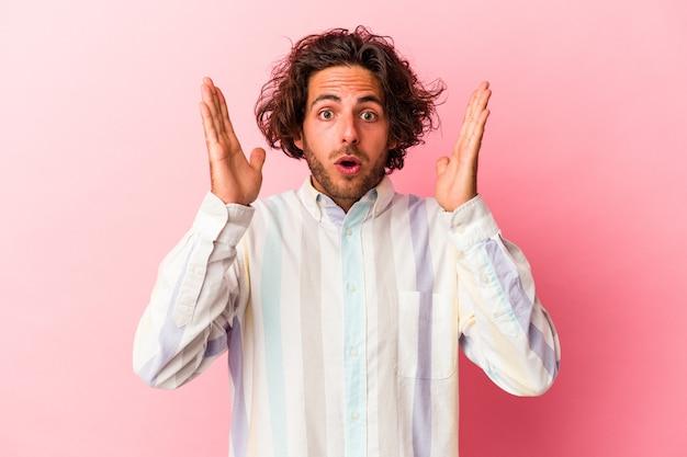 Młody człowiek kaukaski na białym tle na różowym bakcground zaskoczony i zszokowany.