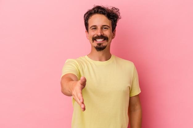 Młody człowiek kaukaski na białym tle na różowym tle, rozciągając rękę na aparat w geście pozdrowienia.
