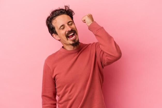Młody człowiek kaukaski na białym tle na różowym tle świętuje zwycięstwo, pasję i entuzjazm, szczęśliwy wyraz.