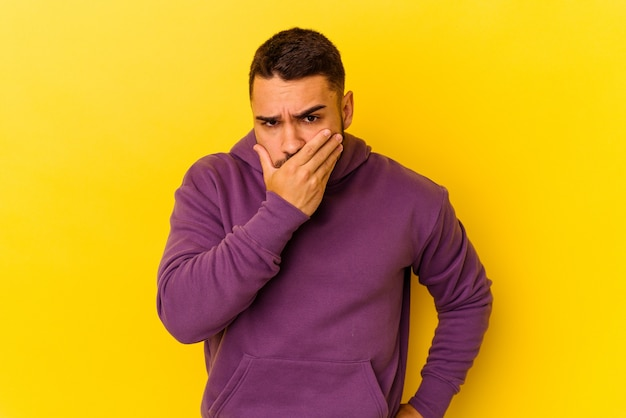 Młody człowiek kaukaski na białym tle na żółtym tle obejmujące usta rękami patrząc zmartwiony.