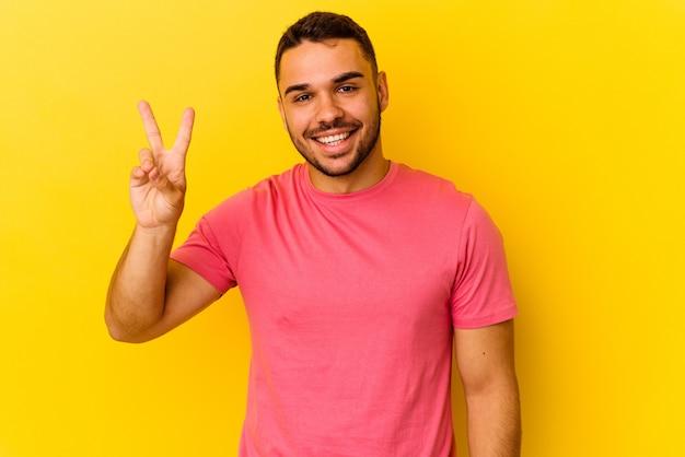 Młody człowiek kaukaski na białym tle na żółtym tle radosny i beztroski pokazując symbol pokoju palcami.