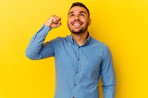 Młody człowiek kaukaski na białym tle na żółtym tle świętuje zwycięstwo, pasję i entuzjazm, szczęśliwy wyraz.