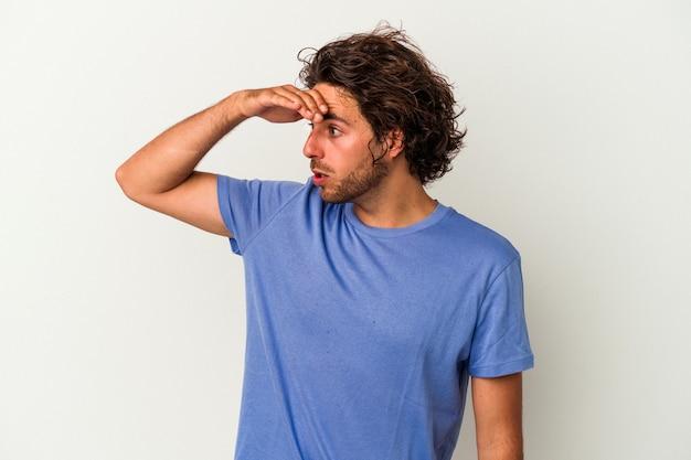 Młody człowiek kaukaski na białym tle patrząc daleko, trzymając rękę na czole.