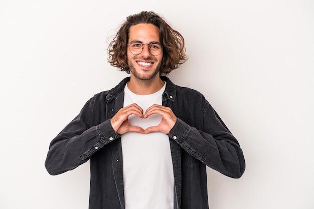 Młody człowiek kaukaski na białym tle uśmiechając się i pokazując kształt serca rękami.