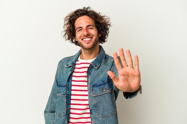 Młody człowiek kaukaski na białym tle uśmiechający się wesoły pokazując numer pięć palcami.