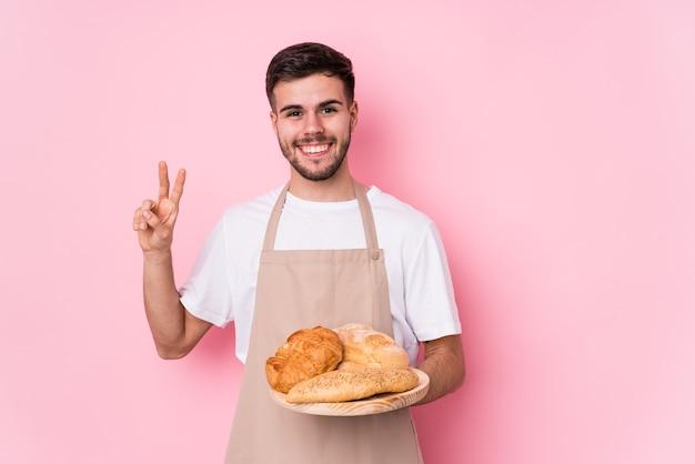 Młody człowiek kaukaski piekarz na białym tle wyświetlono numer dwa palcami.