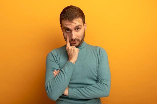 Młody człowiek kaukaski pociągając powiekę w dół na białym tle na pomarańczowej ścianie z miejsca na kopię