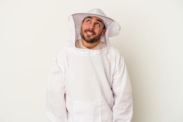 Młody człowiek kaukaski pszczelarstwa na białym tle na białej ścianie marzy o osiągnięciu celów i celów