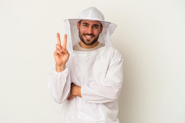 Młody człowiek kaukaski pszczelarstwa na białym tle na białej ścianie pokazuje numer dwa palcami