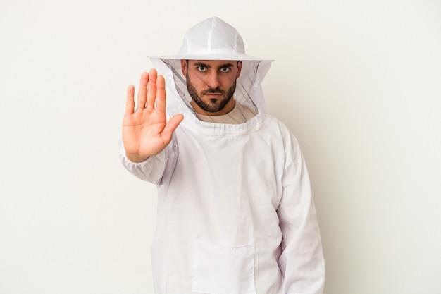 Młody człowiek kaukaski pszczelarstwa na białym tle na białej ścianie stojącej z wyciągniętą ręką pokazujący znak stopu, uniemożliwiając ci
