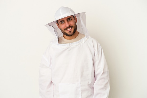 Młody człowiek kaukaski pszczelarstwa na białym tle na białej ścianie szczęśliwy, uśmiechnięty i wesoły