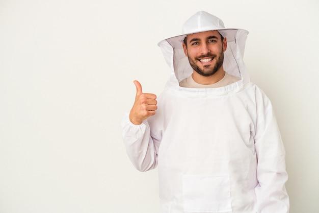 Młody człowiek kaukaski pszczelarstwa na białym tle na białym tle uśmiechnięty i podnoszący kciuk do góry