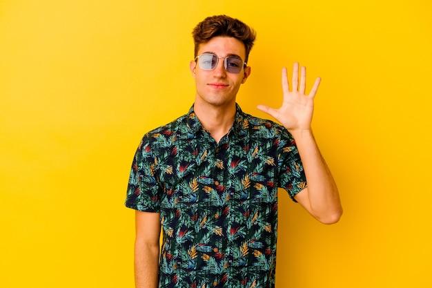Młody człowiek kaukaski sobie hawajski koszula na białym tle na żółtym tle uśmiechający się wesoły, pokazując numer pięć palcami.