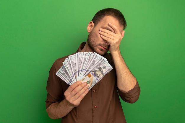 Młody człowiek kaukaski trzymając pieniądze obejmujące oczy ręką na białym tle na zielonym tle z miejsca na kopię