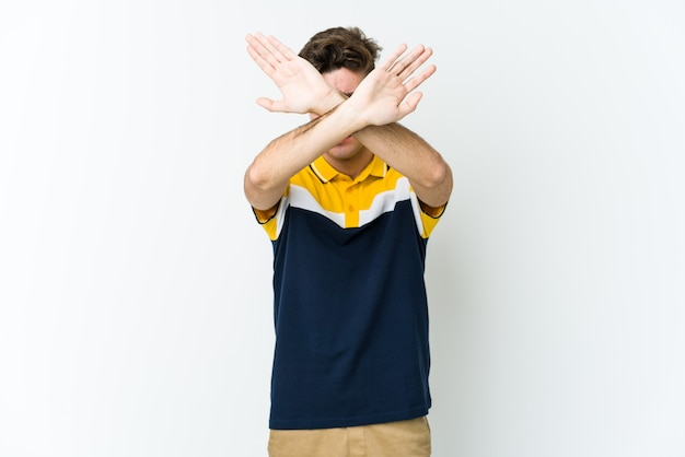 Młody człowiek kaukaski trzymając skrzyżowane ręce, koncepcja odmowy.