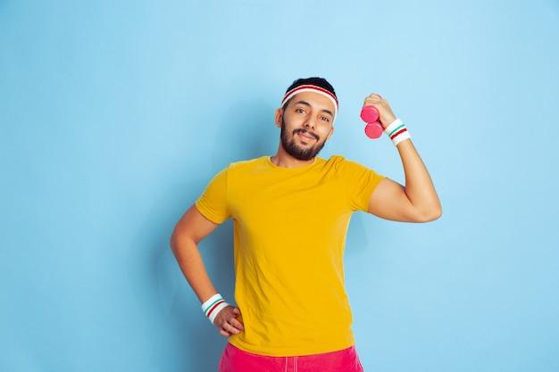 Młody człowiek kaukaski w jasne ubrania szkolenia na niebieskim tle pojęcie sportu, ludzkie emocje, wyraz twarzy, zdrowy styl życia, młodzież, sprzedaż. trening z kolorowymi ciężarkami. copyspace.