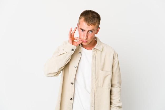 Młody człowiek kaukaski wyrażający emocje na białym tle