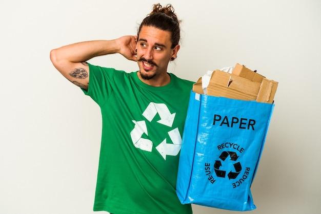 Młody człowiek kaukaski z długimi włosami recyklingu kartonu na białym tle dotykając tyłu głowy, myśląc i dokonując wyboru.