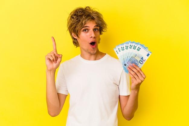 Młody człowiek kaukaski z makijażem gospodarstwa rachunki na białym tle na żółtym tle o pomysł, koncepcja inspiracji.