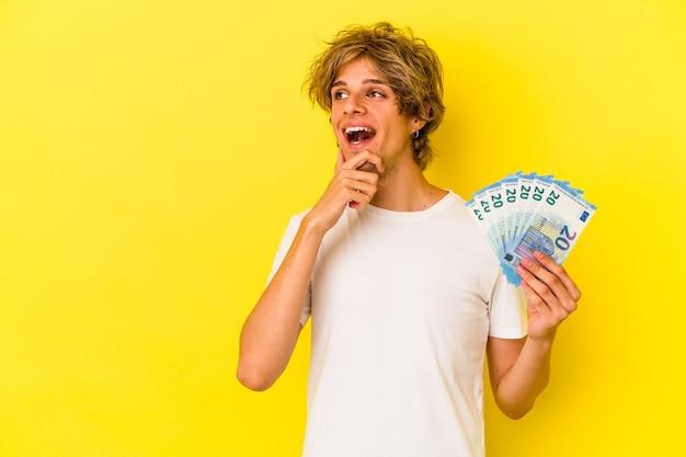 Młody człowiek kaukaski z makijażem gospodarstwa rachunki na białym tle na żółtym tle patrząc w bok z wyrazem wątpliwości i sceptyczny.