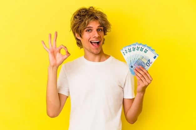 Młody człowiek kaukaski z makijażem gospodarstwa rachunki na białym tle na żółtym tle wesoły i pewny siebie pokazując ok gest.