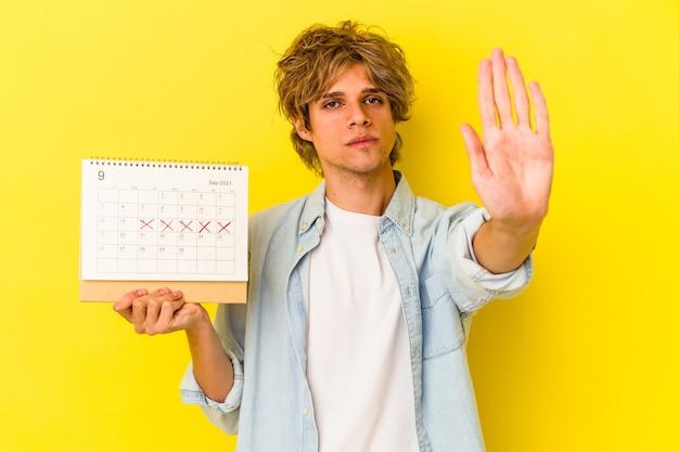 Młody człowiek kaukaski z makijażem trzymając kalendarz na białym tle na żółtym tle stojący z wyciągniętą ręką pokazując znak stop, uniemożliwiając.