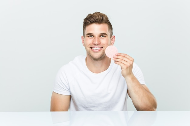 Młody człowiek kaukaski za pomocą gąbki do twarzy.