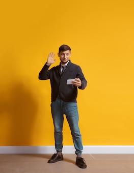 Młody człowiek kaukaski za pomocą smartfona portret długości całego ciała na białym tle nad żółtą ścianą