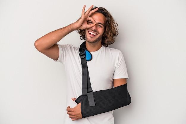 Młody człowiek kaukaski ze złamaną ręką na białym tle na szarym tle podekscytowany, trzymając ok gest na oko.