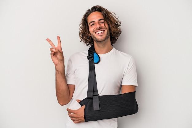 Młody człowiek kaukaski ze złamaną ręką na białym tle na szarym tle radosny i beztroski pokazując symbol pokoju palcami.