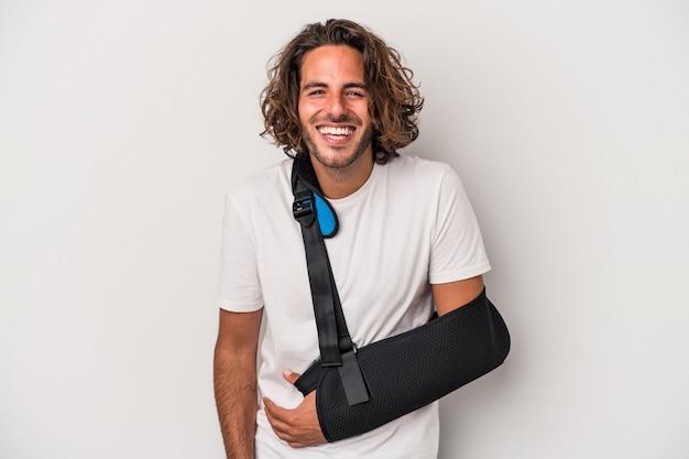 Młody człowiek kaukaski ze złamaną ręką na białym tle na szarym tle śmiechu i zabawy.