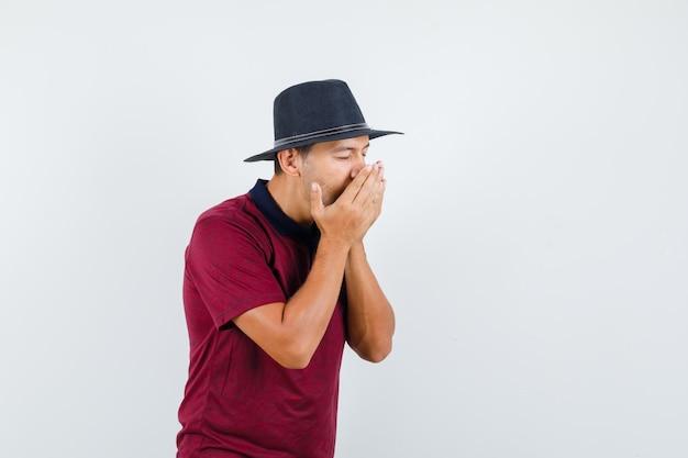 Młody człowiek kicha i ma grypę w koszulce, kapeluszu i wygląda na chorego. przedni widok.