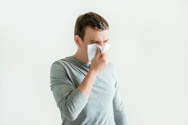 Młody człowiek kichanie w chusteczce dmuchanie wycieranie katar, objawy zakaźne układu oddechowego, objawy grypy i koronawirusa