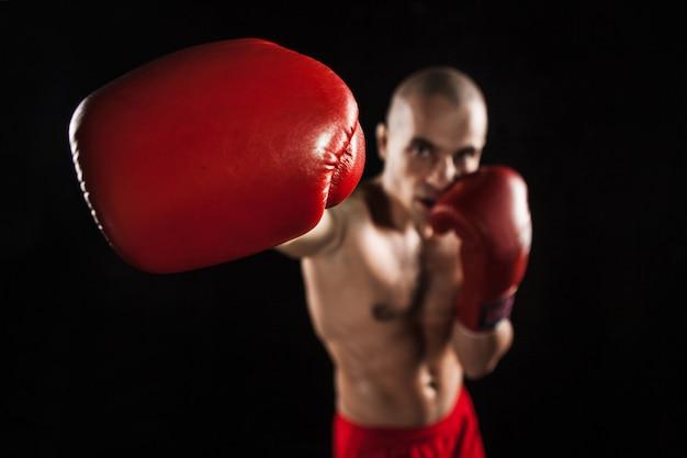 Młody człowiek kickboxing na czarno z kapą w ustach