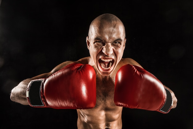 Młody człowiek kickboxing na czarno z wrzeszczącą twarzą