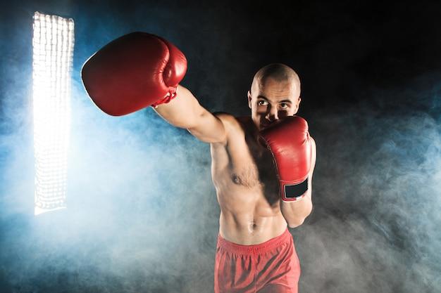Młody człowiek kickboxing w błękita dymu