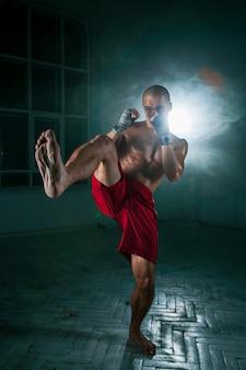 Młody człowiek kickboxing w niebieski dym