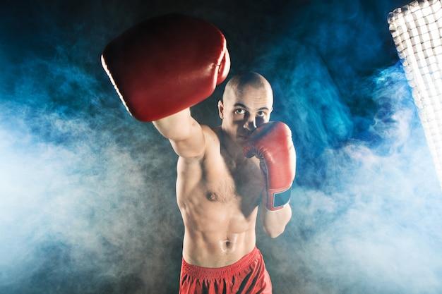 Młody człowiek kickboxing w niebieskim dymie