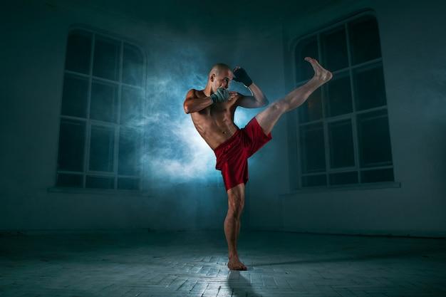 Młody człowiek kickboxing w niebieskim dymu