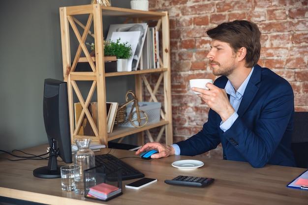 Młody człowiek, kierownik, zespół po kwarantannie wrócił do pracy w swoim biurze, czuje się szczęśliwy i zainspirowany
