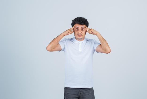 Młody człowiek kładzie palce na skroniach w białej koszulce i dżinsach i wygląda poważnie, widok z przodu.