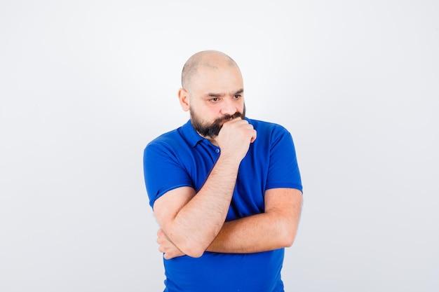Młody człowiek, koncentrując się na czymś w niebieskiej koszuli i patrząc zamyślony, widok z przodu.