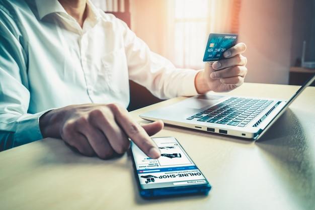 Młody człowiek korzysta z karty kredytowej na zakupy online
