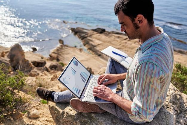 Młody człowiek korzysta ze swojego laptopa i notatnika podczas pracy zdalnej na wybrzeżu