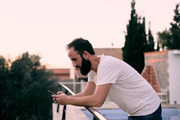 Młody człowiek korzystający z aplikacji do czatu w swoim leśnym domu