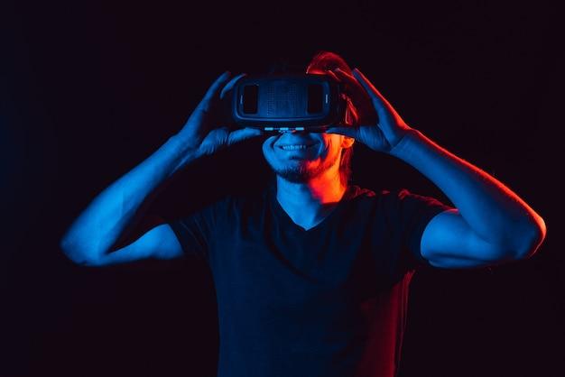 Młody człowiek korzystający z nowoczesnych okularów wirtualnej rzeczywistości.