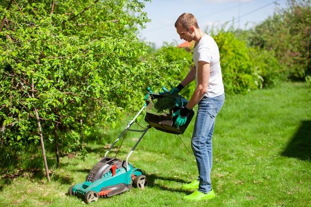 Młody człowiek koszenia trawnika. pracownik wykonuje swoją pracę na podwórku.