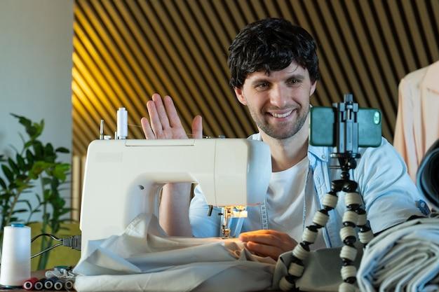 Młody człowiek kręci lekcję wideo szyjącą na maszynie do szycia prowadzi bloga o szyciu