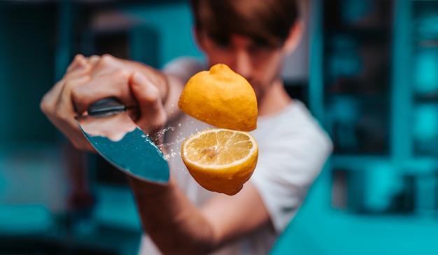 Młody człowiek krojenie z ostrym nożem latający soczysty świeży cytryna
